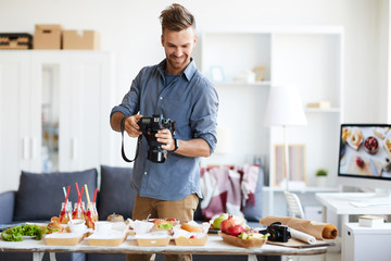 Waist up portrait of handsome photographer taking pictures of party table in photo studio, copy space