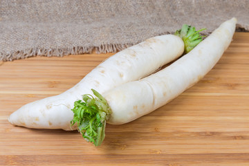 Two fresh daikon radish on wooden surface at selective focus