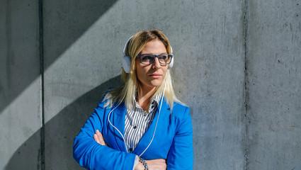 Businesswoman with headphones posing in the street