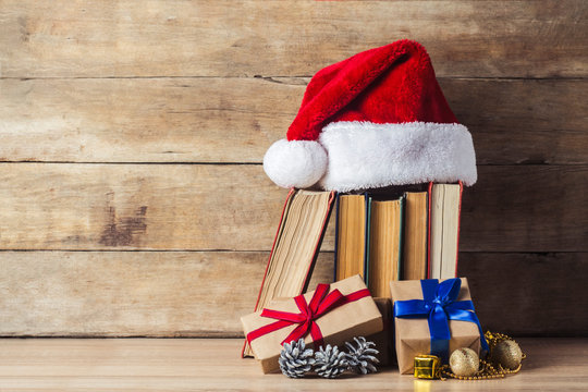 A stack of books, Santa Claus's cap, an alarm clock, cones, Christmas-tree decorations, gift boxes on a wooden background. Concept of New Year and Merry Christmas.