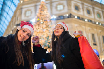 Young women friends shopping together before Christmas