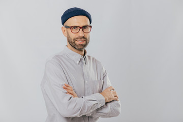 Isolated shot of pleasant looking unshaven male keeps hands crossed, wears stylish hat, optical glasses, models over white background with copy space for your advertising content, enjoys leisure