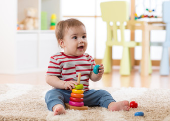Cute baby playing with pyramid toy in nursery