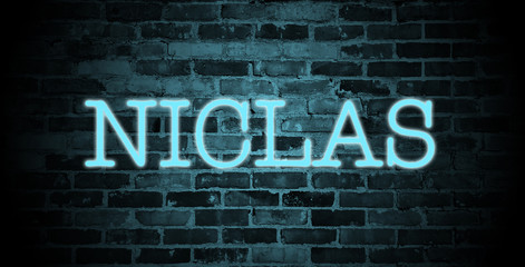 first name Niclas in blue neon on brick wall