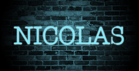 first name Nicolas in blue neon on brick wall