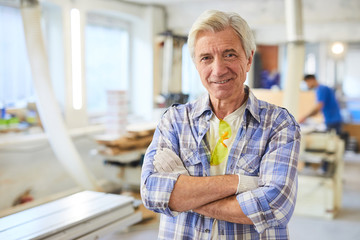 Smiling content handsome mature carpenter with wrinkles wearing checkered shirt and work gloves standing in workshop and looking at camera
