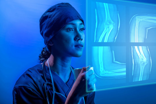 Young asian doctor woman looking at digital ct scan on virtual screen