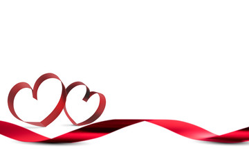 Red ribbons with ribbons shaped as hearts over white background