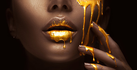 Zelfklevend Fotobehang Fashion Lips Golden paint smudges drips from the face lips and hand, golden liquid drops on beautiful model girl's mouth, creative abstract makeup. Beauty woman face