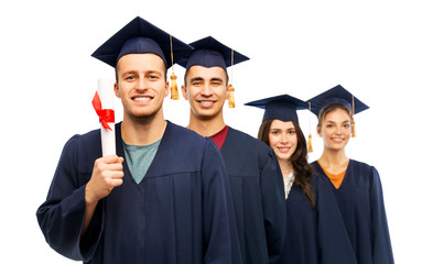 education, graduation and people concept - group of happy graduate students in mortar boards and bachelor gowns with diploma over white background