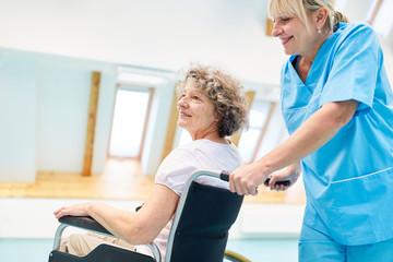 Pflegekraft betreut eine Senior Frau im Rollstuhl
