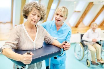 Therapeutin hilft Seniorin mit dem Rollator