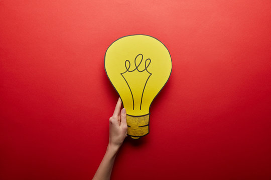 top view of yellow light bulb made from paper idea symbol on red background