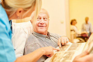 Mann mit Alzheimer betrachtet Fotoalbum