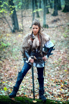 Dangerous woman warrior in woods wearing fur collar and specific makeup holding ax and shield, ready to attack