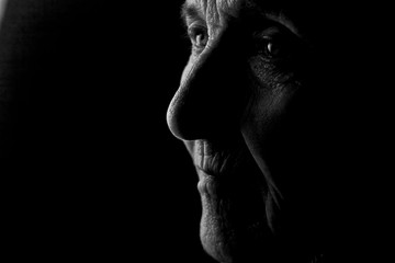 Portrait of an old grandmother's face in profile in the dark