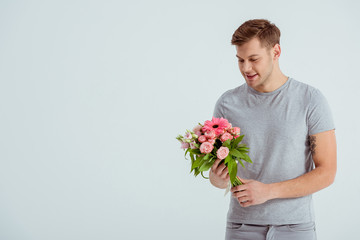 handsome man holding pink flower bouquet with copy space isolated on grey