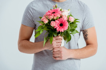 cropped view of man holding pink flower bouquet isolated on grey