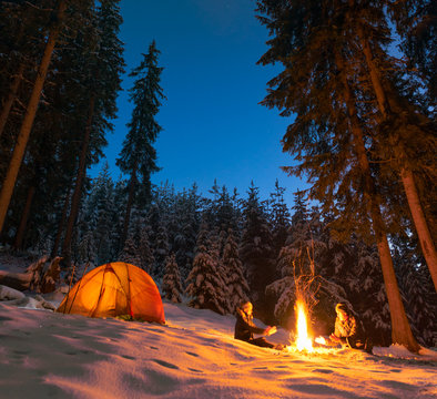 couple camping with campfire and tent outdoors in winter