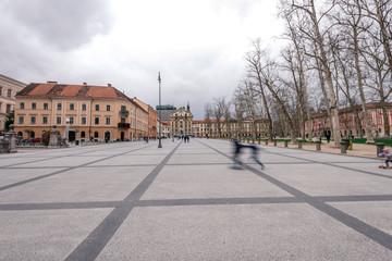 Ljubljana in Slovenia on a cloudy day - River, bund, Ljubljana Castle - blurred people