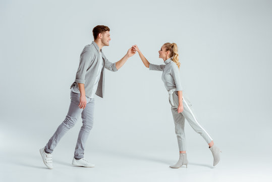 beautiful couple holding hands and looking at each other while dancing isolated on grey