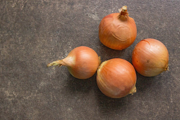 4 onions on a brown stone table, close-up