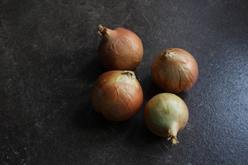 Four onions on a brown stone table, close-up