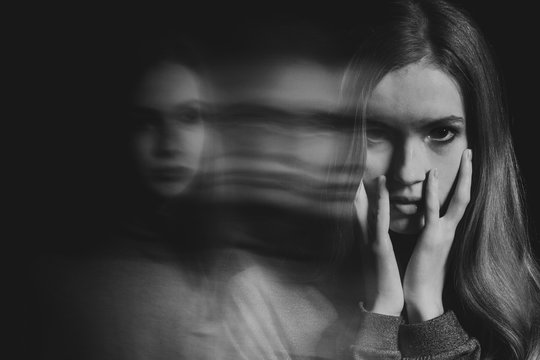 Black and white picture of scared beautiful young redhead woman with post traumatic stress disorder having sleep problems
