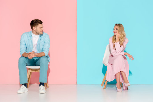 man with folded hands sitting on chair and looking at bored woman touching chin on pink and blue background
