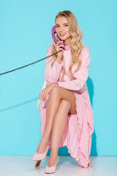 beautiful woman with legs crossed talking on vintage telephone with turquoise background