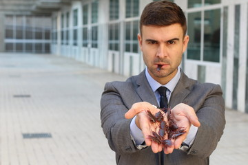 Businessman holding and eating roaches