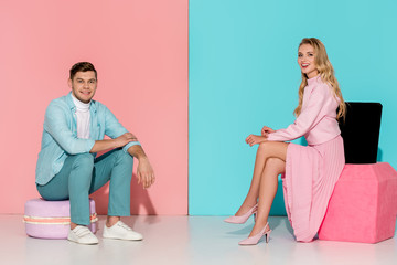 couple sitting on big macaroon and nail polish models while looking at camera on pink and blue background