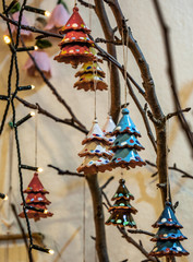 branches of a tree decorated with small Christmas trees, lights and other small objects