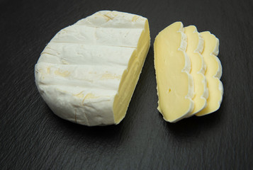 Camembert. Soft creamy cheese sliced on dark background