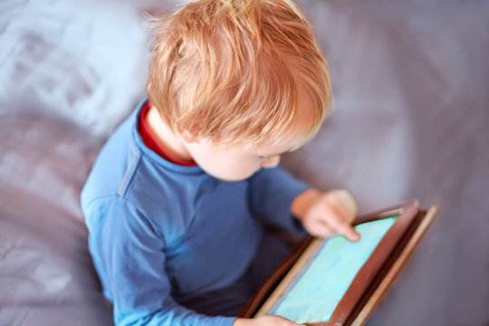 Little caucasian baby boy sits on the sofa using a tablet, touching screen. Red hair, casual wear, indoors, close up, copy space. Children time spending, computerization of youngsters concept.