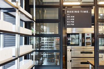 Modern pastry kitchen entrance decorated in black, white and steel with baking schedule board.