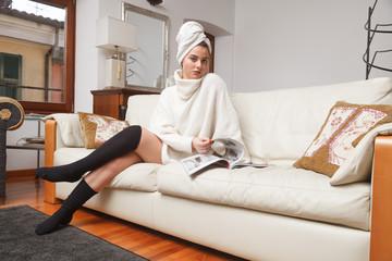 bella donna sfoglia rivista sul divano
