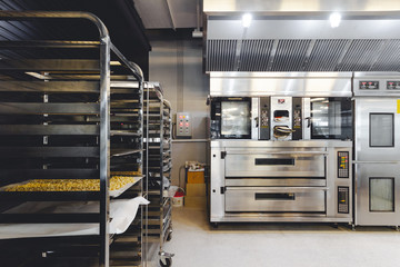 Modern pastry kitchen decorated in black, white and steel with baking machine, oven, conveyor, production line, mixer and cooling plant.