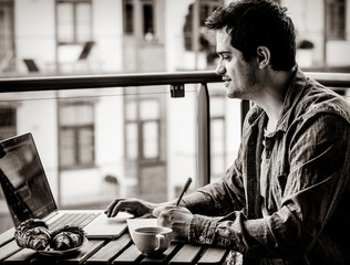 Handsome young manager working on laptop while sitting outdoors at home. Concept of work with startup business