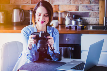 Beautiful young photographer sitting at kitchen with camera. Concept of work with startup business