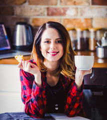 Portrait of young woman with cup of tea or coffee sitting at kitchen in red shirt. Morning time