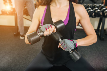 Close-up dumbell in hands fitness woman. Fitness girl pumping up muscles with dumbbells.