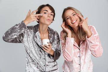 Two cheerful girls wearing pajamas standing