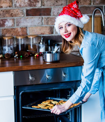 Beautiful young woman in Santa Claus hat with baking tray full of cookies at kitchen. Christmas time