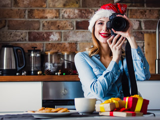 Beautiful young photographer sitting and at kitchen with camera and present gifts. Christmas time
