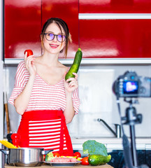 Young caucasian blogger woman cooking at camera for Video-sharing website. Home location at kitchen