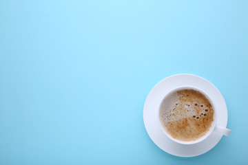 Cup of coffee on blue background, flat lay