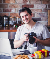 handsome man with cup of tea or coffee and laptop computer holding camera sitting at kitchen in Christmas time