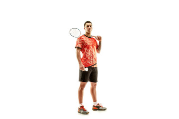 Young man badminton player standing over white studio background. Fit male athlete