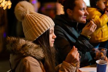 Teenager enjoying traditional food at Christmas market in Zagreb, Croatia.